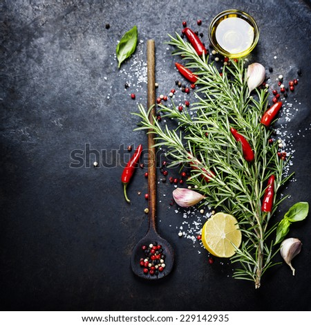 Bunch of spices  and old spoon on dark vintage background. Cooking, vegetarian food or health concept. - stock photo