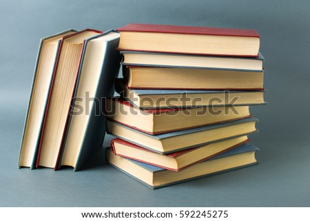 Bunch of stacked books against blue background