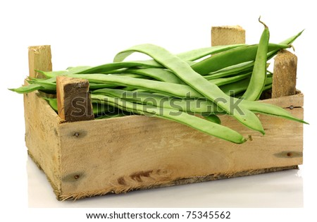 bunch of string beans in a wooden box on a white background