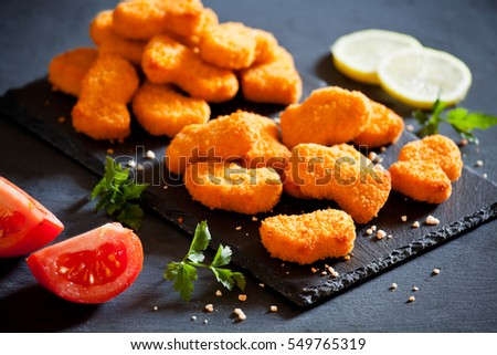 Bunch of tasty chicken nuggets on a slate plate