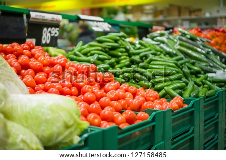 Bunch of tomatoes and cucumbers on boxes in supermarket - stock photo