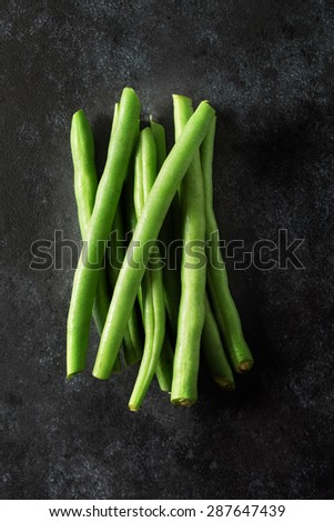 Bunch of trimmed fine green beans shot from above on dark background
