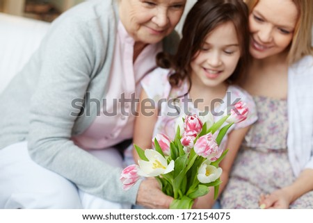 Bunch of tulips held by senior woman with her daughter and granddaughter near by - stock photo