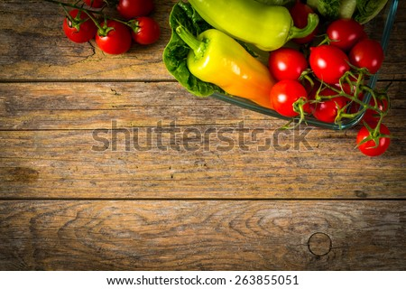 Bunch of vegetables in the glass jar. Red tomato, yellow pepper and green salad on wooden table.