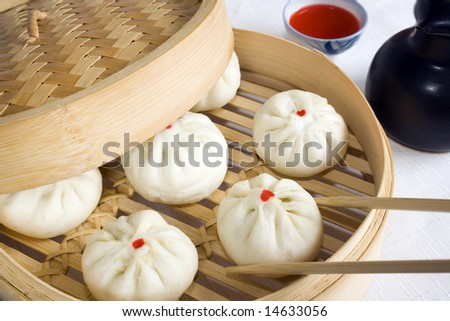 Bunch of vegetarian stuffed dumplings on a bamboo steamer. Main focus on the dumpling with chopsticks. - stock photo
