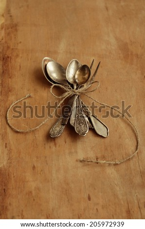 Bunch of vintage spoons and lemon fork tied up with jute rope and decorated with bow over aged background