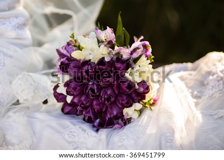 bunch of white and purple flowers lying on a wedding dress, on a white background, wedding accessories, wedding preparation, wedding flowers - stock photo