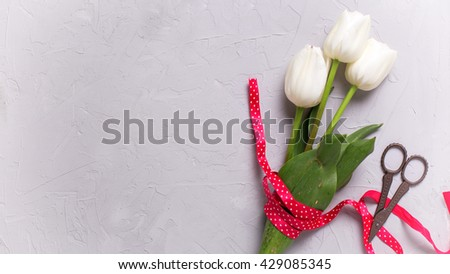 Bunch of white tulips flowers with red ribbon and scissors on grey textured  background. Flat lay with copy space. Selective focus. Toned image. - stock photo