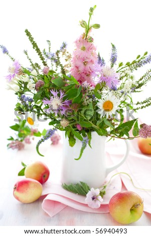 bunch of wild herbs, flowers in a  jug and apples - stock photo