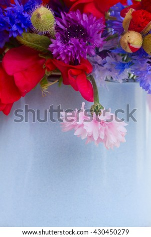 Bunch of wildflowers in blue pot close up on wooden background - stock photo