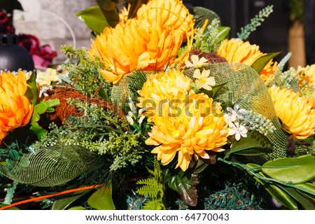 Bunch of yellow artificial flowers lying on a grave - stock photo
