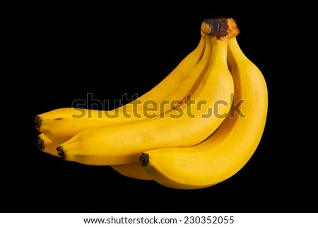 bunch of yellow ripe bananas isolated on a black background - stock photo