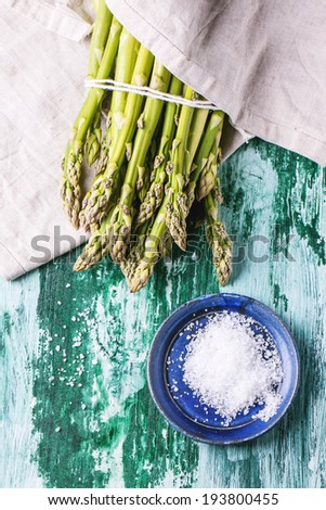 Bunch of young green asparagus with ceramic plate of sea salt over green wooden table. Top view. - stock photo