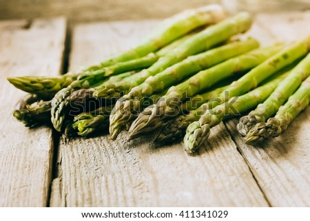 Bunches of asparagus on a wood background. - stock photo