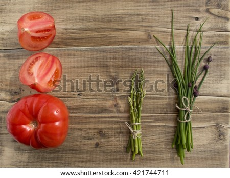 bunches of fresh onion, asparagus and large tomatoes - stock photo