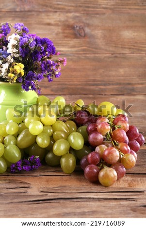 Bunches of ripe grapes and vase of fresh flowers on wooden table on wooden wall background - stock photo