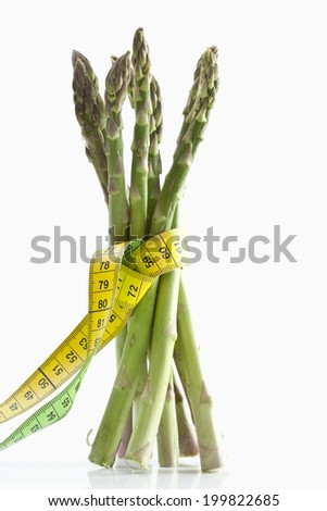 Bundle of asparagus wrapped in measuring tape against white background - stock photo