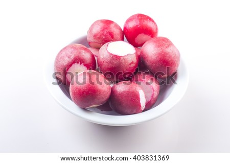 Bundle of bright fresh organic radishes in a bowl over white background - stock photo