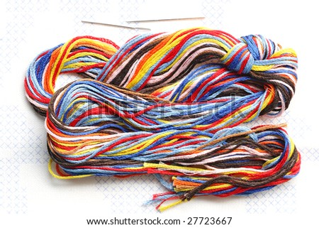 Bundle of colorful embroidery threads on stamped cross stitch