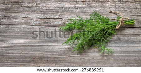 Bundle of dill herb on rustic wooden background. Food ingredient - stock photo