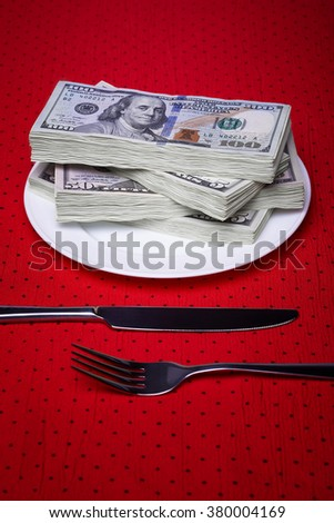 Bundle of dollars on a plate, paper money, an economic concept, serving business lunch, a red tablecloth in a black polka dots.
