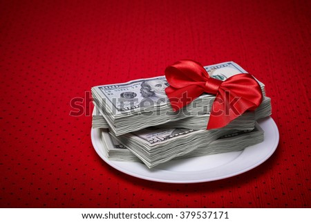 Bundle of dollars on a plate, paper money, red bow of the braid, economic concept, serving business lunch, a red tablecloth in a black polka dots.