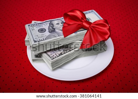 Bundle of dollars on a plate, paper money, red bow of the braid, economic concept, serving business lunch, a red tablecloth in a black polka dots. - stock photo