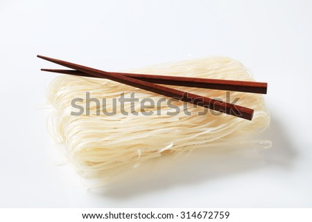Bundle of dried rice noodles and wooden chopsticks - stock photo