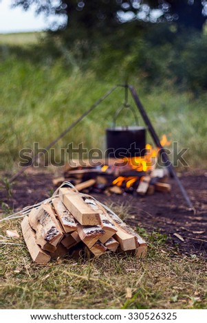 Bundle of firewood on a background of the fire with a pot on a tripod - stock photo