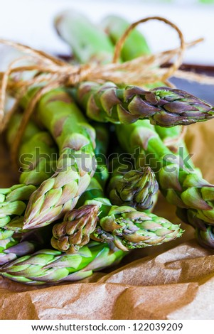 Bundle of fresh asparagus spears tied with string on brown paper