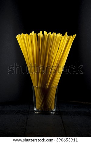 Bundle of italian pasta in glass on dark background.