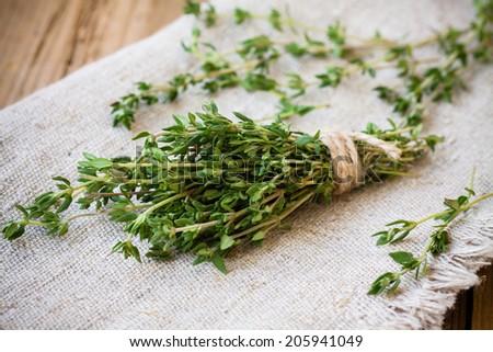 bundle of raw fresh organic thyme on sackcloth - stock photo