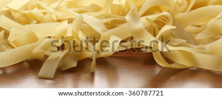Bundle of raw uncooked Italian pasta macaroni lying on wooden surface with shallow dof   - banner / header edition - stock photo