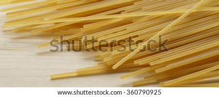 Bundle of raw uncooked Italian pasta spaghetti macaroni lying on a textured wooden surface with shallow dof and focus to the ends of the strands with space for text  - banner / header edition    - stock photo