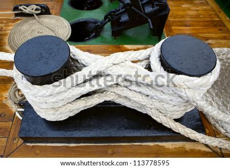 Bundle of rope on the black  bollard - stock photo