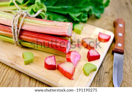 Bundle of stalks rhubarb, rhubarb pieces with a sheet, a knife on a wooden boards background - stock photo
