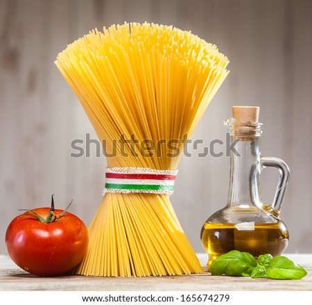 Bundle of uncooked dried Italian spaghetti tied with a ribbon in the colours of the national flag - red, white and green - on a kitchen counter with fresh basil leaves, tomato and a jar of olive oil - stock photo