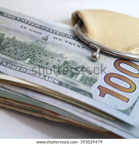 Bundle of US dollars banknotes sticking out of a small wallet, still-life with selective focus - stock photo