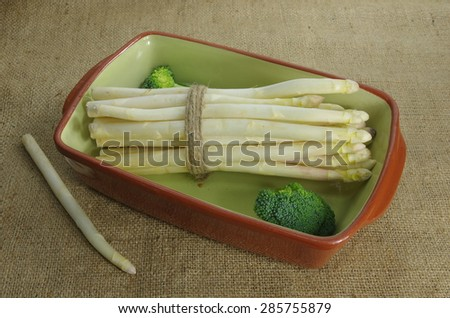 bundle of white asparagus and   broccoli in bowl - stock photo