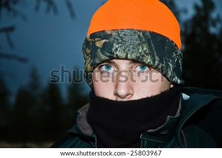 Bundled up teen boy on an early morning deer hunt, dressed for the cold weather.