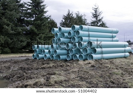 Bundles of blue PVC pipe ready for the sewer or water line. - stock photo