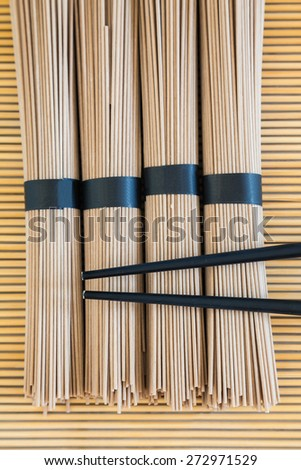 bundles of buckwheat soba noodles and black chopsticks on bamboo background