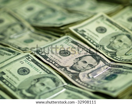Bundles of U.S. Five Dollar bill laid out as a background - stock photo