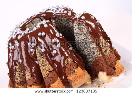 Bundt Cake, covered with chocolate and silver sugar balls, with a cut slice - stock photo