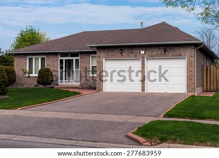 Bungalow home with a lawn and driveway - stock photo