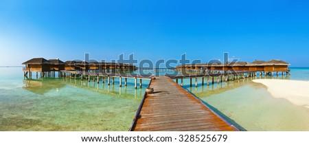 Bungalows on tropical Maldives island - nature travel background - stock photo