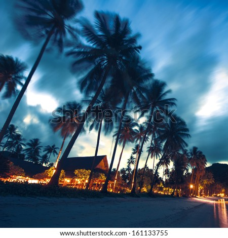 Bungalows, palms and beach at sunset in thailand paradise - stock photo