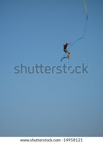 Bungee jumper high up in the sky - stock photo