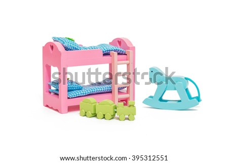 Bunk bed with stairs, blankets & pillows, miniature rocking horse & wooden train. Toy bedroom for dollhouse. Mini furniture for children learning to decorates there bedroom an image isolated on white - stock photo