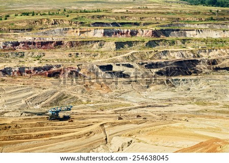 Bunk wall surface mine with exposed colored minerals and brown coal, mining equipment at the bottom the pit, view from above, top view - stock photo